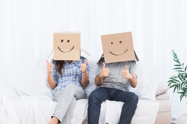 Couple sitting with cardboard boxes with smiley faces on head gi