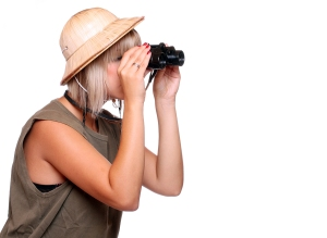 Young woman watching closely wildlife with his binoculars. Studi