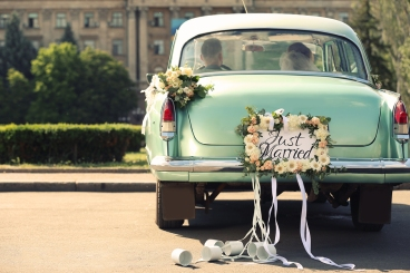 Wedding couple in car decorated with plate JUST MARRIED and cans