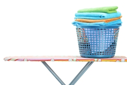 A laundry basket full of clothes on ironing board isolated on wh